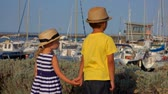 sailboat : Little boy and girl in a straw hat is looking on the yacht port Stock Footage