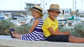 sailboat : Children sit on a bench back to back and smile at the camera