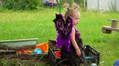 borboletas : Little cute blond girl with butterfly wings plays near the sandbox Stock Footage