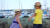 sailboat : Little boy and girl in hats play on the quay of the yacht port