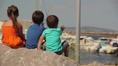 sailboat : Children are sitting on the stone and looking at the bay with yachts. View from the back Stock Footage