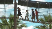 spielplatz : Group of children overcome the obstacle in the playground. Kids are walking on a suspension bridge at a height. Adventure at the playground