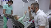 diente : Blond girl gives dentist a high five after checking her teeth. Dental clinic Archivo de Video