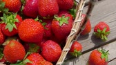 ハング : Panorama of a wooden table with strawberries and baskets full of juicy red berries on a bright sunny day 動画素材