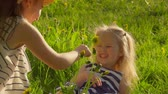 ensemble : Two wonderful girls playing with dandelion flower in the garden at sunset