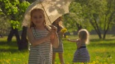ensemble : Beautiful girl plays with an umbrella, while her sisters pick flowers in the park
