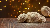 noel : Meringue cookies fall on a wooden surface on a background of Christmas lights