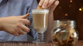 escuro : Woman takes cantucci cookies from a glass jar and dips it in latte coffee