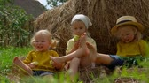 humor : Three little girls having fun, laughing and playing feet on a haystack