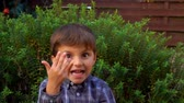 inocente : Cheerful boy counts on fingers, shows thumbs up, plays and has fun outdoors. Five year old boy smiles