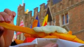 belga : Hand takes french fries and dips it in sauce on the background of an old Belgian building with flags Stock Footage