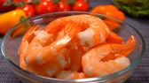 aquaculture : Hand puts delicious large shrimp in a glass bowl against tomatoes and peppers