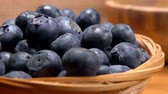 agrio : Hand puts big mouth-watering ripe blueberries in a basket on the background of burlap