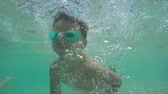 aquático : Little boy in swimming goggles learning to swim and dives under water Stock Footage