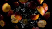 abricot : Halves of a peach fly and bounce in splashes of water on a black background