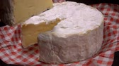 delicadeza : Sliced piece of soft camambert cheese is taken out with a knife from whole cheese on a red-white vichy napkin