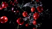 Appetizing juicy cherries bounce up with splashes of water on a black background