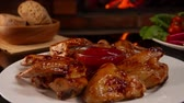 ali di pollo : Close up of a plate with grilled chicken wings on a background of a burning fireplace
