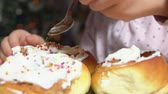 Little girls hand throws a sprinkle on cinnamon roll with cream on the background of christmas tree