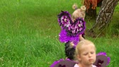 fadas : Two girls in a violet butterfly costumes walking on the green lawn. Children pretend to be purple butterflies