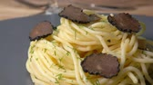 tartufo nero : Close up of a spagetti pasta sprinkled with slices of a black truffle fungus on a grey plate
