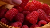 vime : Close up of a large juicy appetizing raspberries in a wicker basket on a wooden table
