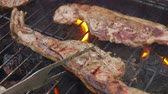 чеснок : Pieces of half-prepared meat steak are flipped on the grill with flames Стоковые видеозаписи