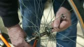 soustružení : a man takes a bicycle wheel off its frame Dostupné videozáznamy