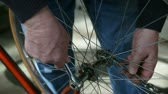 горизонтальный : a man making adjustments to his bike wheel Стоковые видеозаписи