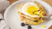 yaban mersini : Cutting into a breakfast of blueberry pancakes topped with a fried egg