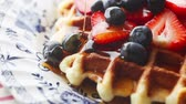 Closeup of syrup poured over waffle with strawberries and blueberries on a decorative plate Stok Video