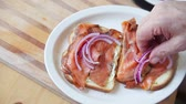 A man puts thinly-sliced red onions on a fish sandwich with copy space Wideo