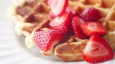 Adding fresh sliced berries to a homemade waffle Wideo