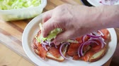 A man adds shredded lettuce to a sandwich