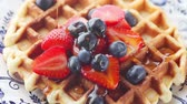 Overhead of syrup poured over fresh fruit on homemade waffle