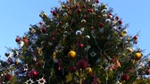 отраженный : A big Christmas tree against the sky. Decorated Christmas tree.