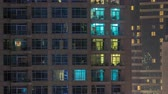 balcony view : Windows of the multi-storey building of glass and steel lighting inside and moving people within timelapse
