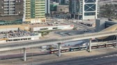 bonde : Aerial view of Metro station near Jumeirah lakes towers skyscrapers timelapse with traffic on sheikh zayed road.