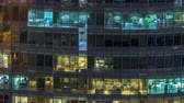 organização : Windows of the multi-storey building of glass and steel lighting inside and moving people within timelapse
