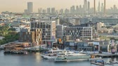 vu d en haut : Dubai creek landscape timelapse with boats and ship near waterfront and modern buildings in the background during sunset
