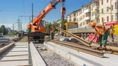 mounted : Orange construction telescopic mobile crane unloading tram rails from truck timelapse.