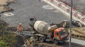 urban renewal : Concrete works for road construction with many workers and mixer timelapse