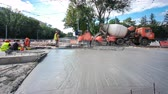 urban renewal : Concrete works for road construction with many workers and mixer timelapse hyperlapse