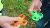 woede : trendy fidget spinner - two persons holding spinning green and orange fidget spinners in hands, close up view Stockvideo