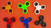 rolamento : fidget spinners spinning by someones hand on orange background, popular relaxing toy, generic design Stock Footage