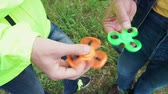 trendy fidget spinner - two persons holding rolling green and orange fidget spinners in hands