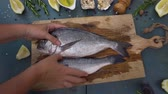 seabass : Someones hands placing and showing raw fish breams