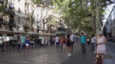 kozmopolita : BARCELONA, SPAIN - JULY 12, 2017: Crowd of people walking, meating anf resting on La Rambla street in central Barcelona at summer day, popular with tourists and locals alike, Barcelona, Spain, slow motion Stock mozgókép