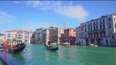 VENICE, ITALY - MARCH 23, 2018: People taking strall in gondolas and boats in front of Giant Hands of Venice s Grand Canal, view from the water, Italy muticolored Venice houses over water of Grand canal, view from the water, Italy