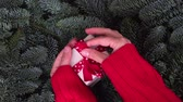 Christmas gift giving - someones hand in red sweater holding and opening white gift box with present Vídeos